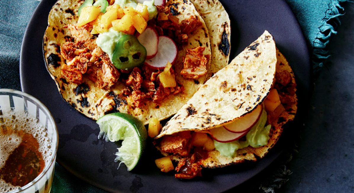 Fish taco recipe using canned tuna, topped with mango salsa, avocado crema, and fresh lime.